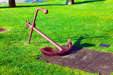 Rusty boat anchor on green grass Stock Photo