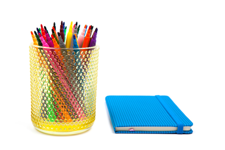 Notebook and multicolored markers on a white background