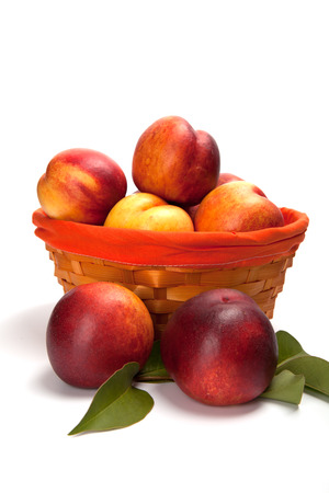 Fresh fruit nectarines in the basket, on white background