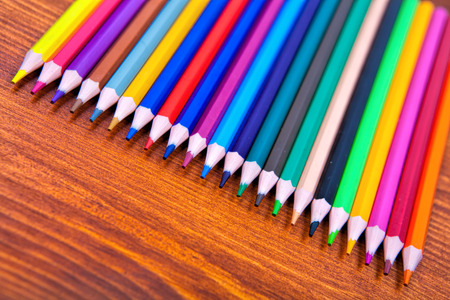 Color pencils on wooden table background. Close up