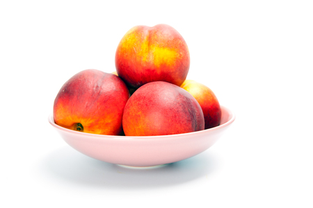 Ripe peaches in bowl isolated on white
