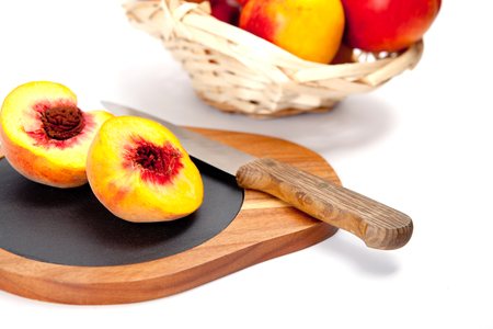 washed: Freshly washed peach  on wooden cutting board with knife Foto de archivo