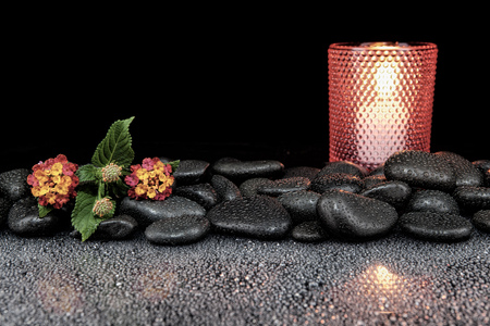 Beautiful spa concept of blooming  flower, candles and black stones