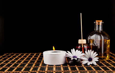 Spa decoration with stones,   candle, with massage oil on a black background Stock Photo