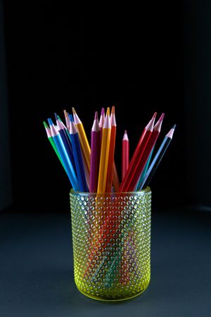 Colors pencil in glass with back background