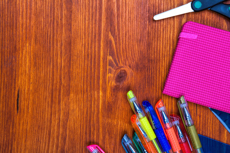 Frame of school supplies on the wooden table, top view