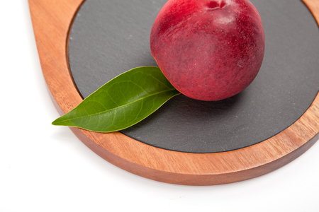 Freshly washed peach  on wooden cutting board isolated on white background