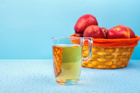 Glass with fresh apple juice on wooden table .