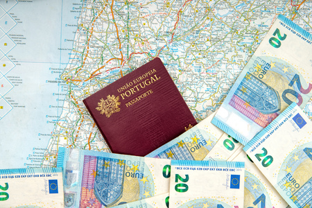 The Portuguese passport and euro banknotes on a geographical map .