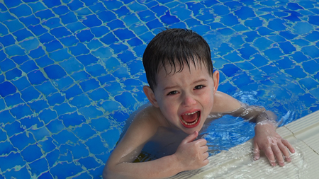 Pretty little boy crying and capricious in swimming pool