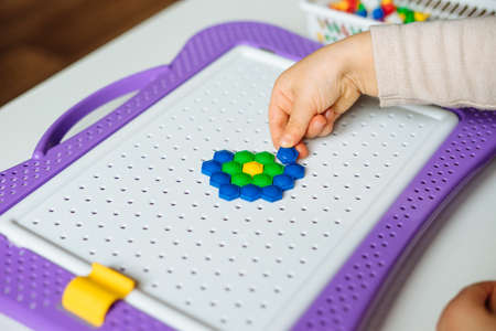 Child is playing with mosaic puzzle at home. Children's creative game for early development and fine motor skills. Fun activities for toddlers. Close up.