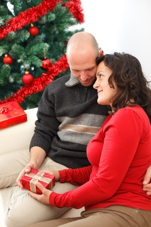 Young man giving a gift to his girlfriend near the Christmas tree photo