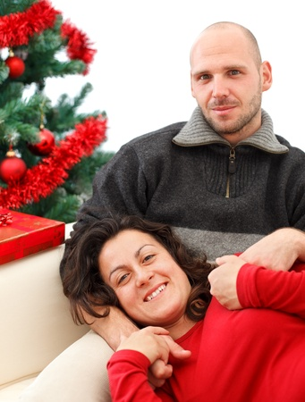 Young happy couple near a Christmas tree photo