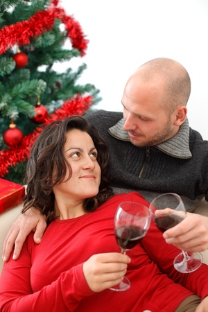 Young couple at sofa celebrating Christmas with a cup of wine photo