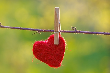 attached: Red heart attached to a clothesline with pin Stock Photo