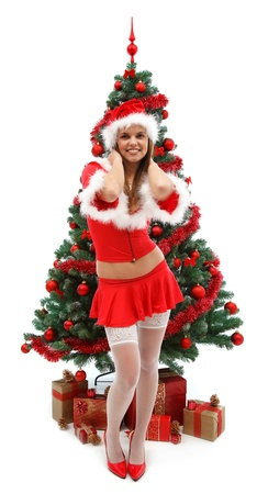 Sexy young woman in santa clothes smiling to us before the Christmas tree, with lots of presents Stock Photo - 8460396