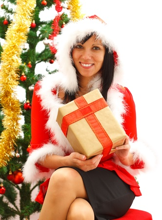 Attractive young female Santa offering a gift near the Christmas tree photo