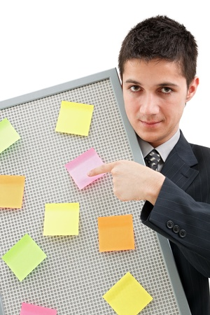 yelloow: A businessman holding a reminder board with plenty of colorful post-it on it