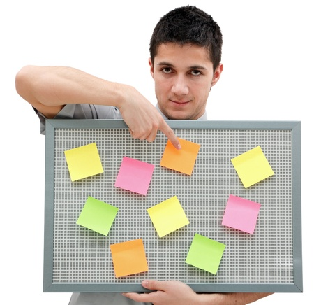 yelloow: A handsome young man holding a reminder board with plenty of colorful post-it on it Stock Photo