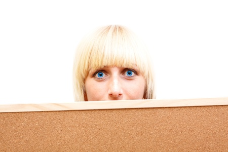 An attractive young girl with blue eyes looking out behind a corkboard photo