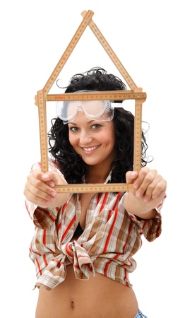 Sexy young repair woman with a folding rule in her hand in form of house photo