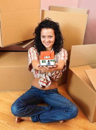 Attractive young woman offering a miniature house, boxes in the background Stock Photo - 9493968