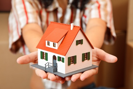 Model house in woman's hand, boxes in the background Stock Photo - 9492758
