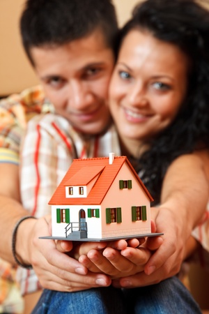 miniature people: Happy young couple offering a miniature house, boxes in the background Stock Photo