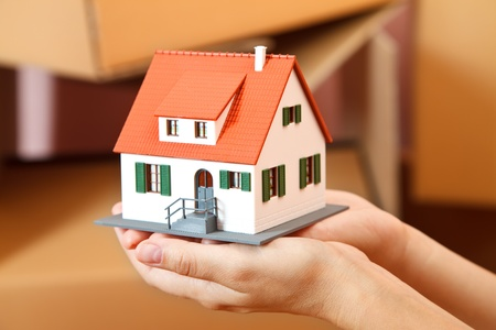Model house in woman's hand, boxes in the background Stock Photo - 9492782