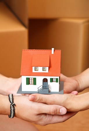 Model house in hand of a couple, boxes in the background Stock Photo - 9492802