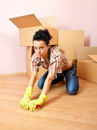 Tired young woman with yellow rubber gloves scrubs the floor Stock Photo - 9490042