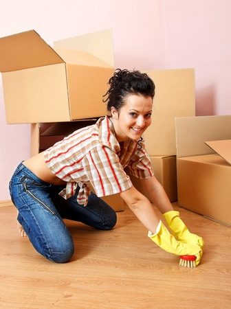 Happy young woman with yellow rubber gloves scrubs the floor Stock Photo - 9494227