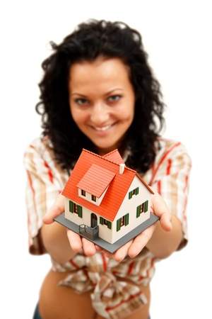 Attractive young woman offering a miniature house Stock Photo - 9493722