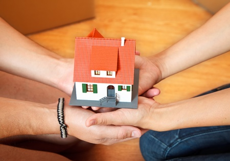 Model house in hand of a couple, boxes in the background Stock Photo - 9492714