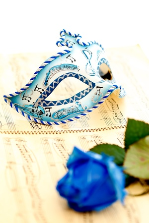 Beautiful carnivale mask on a music paper, by a blue rose photo