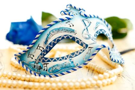 Blaue und weiße Karnevalsmaske auf einem Musikpapier mit Blaurose auf dem Hintergrund