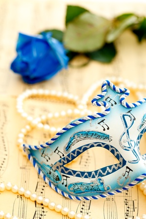 Beautiful mask from Venice on a music paper with blue rose and white pearl photo