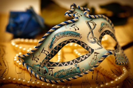 Ornate carnival mask on a music paper with rose and pearl Stock Photo