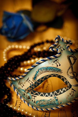Ornate carnival mask on a music paper with rose and pearls Stock Photo