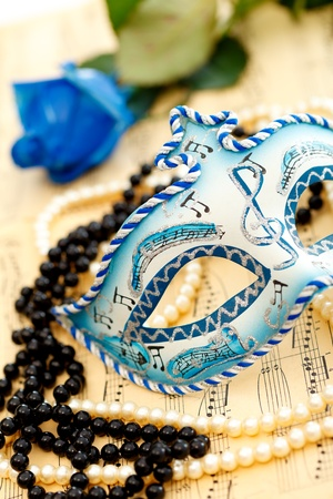 Ornate carnival mask on a music paper with rose, white and black pearls photo