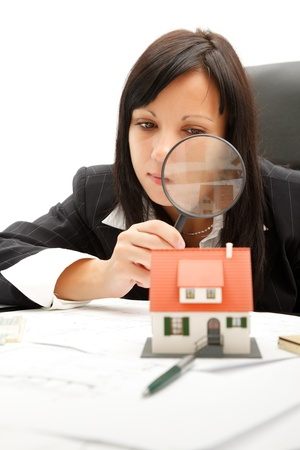 Attractive young business woman inspects a home with magnifying glass photo