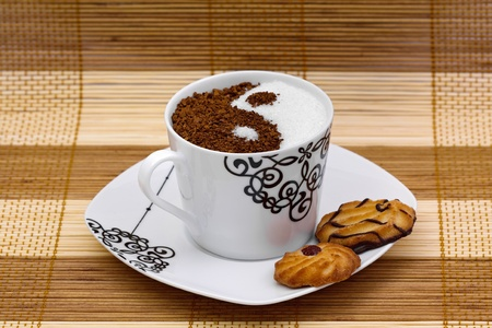 White sugar and brown coffee in a cup with the form of Yin Yang and cookies photo