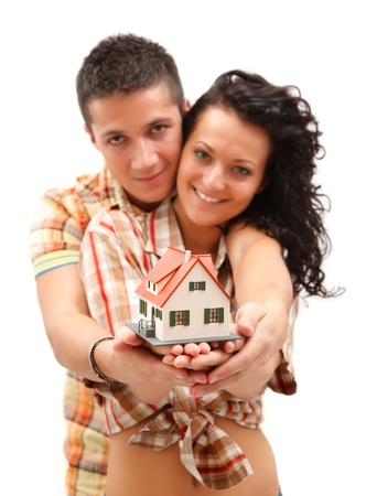 Happy young couple offering a miniature house Stock Photo - 9493704