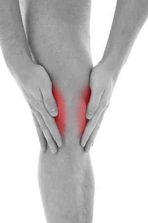 dolor rodillas: Hombre joven con ambas palmas alrededor de rodilla Foto de archivo