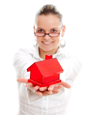 Lovely young woman offering a miniature red house to us, white background Stock Photo - 9493622