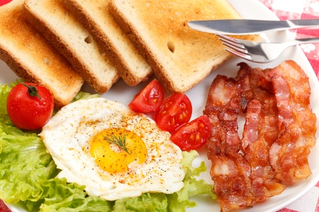 Breakfast of egg, bacon, toast and vegetables