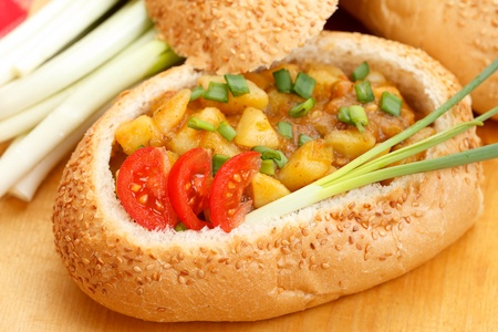 Goulash stew with vegetables served in bread bowl photo