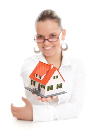 Attractive woman offering a  miniature house to us, focus on the house Stock Photo - 9493621