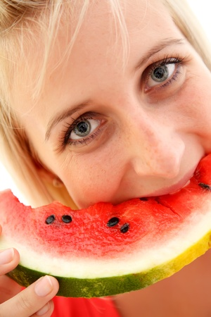 Closeup of a young girl eating watermelon photo