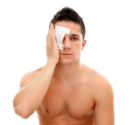 Young man having a gauze bandage on his right eye, isolated on white background photo